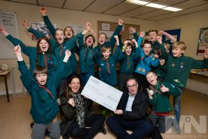 Scout group cheers while holding cheque for £100,000.